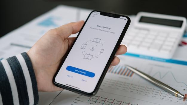 Um funcionário que trabalha em casa está baixando a plataforma social do aplicativo zoom, pronta para reuniões na internet, trabalhadores remotos ou educação on-line