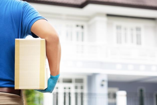 Um funcionário segurando uma caixa está entregando produtos aos clientes em casa.