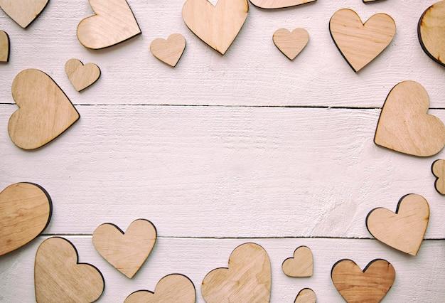 Um fundo bonito com muitos corações de madeira na mesa branca