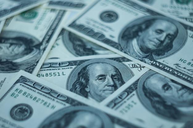 Um fundo de cem dólares espalhados na mesa.