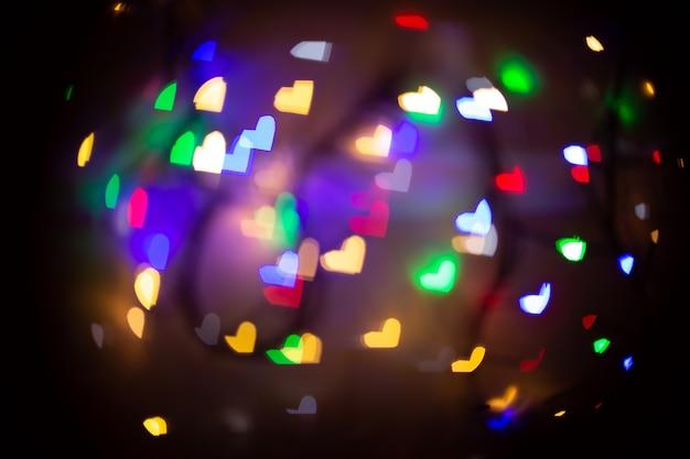 Um fundo desfocado com bokeh em forma de coração em cores diferentes. fundo desfocado