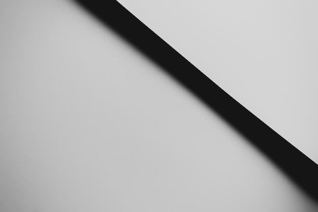 Um fundo plano mínimo em preto e branco com sombras e espaço de cópia para preencher com uma mensagem
