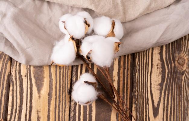 Um galho de madeira morta de algodão em um fundo de madeira com toalha de linho para o design vista superior cópia espaço Foto Premium