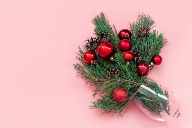 Um galho de uma árvore de natal com bolas de brinquedo vermelhas e cones em um copo isolado em um fundo rosa