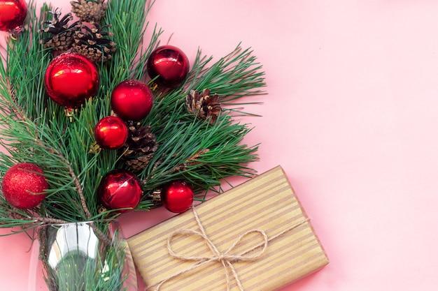 Um galho de uma árvore de natal com bolas de brinquedo vermelhas e cones em um vaso e uma caixa de presente em uma embalagem de artesanato