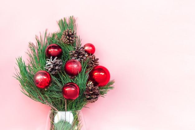 Um galho de uma árvore de natal com bolas de brinquedo vermelhas e cones em um vaso isolado em um fundo rosa