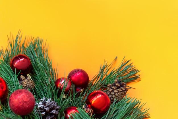 Um galho de uma árvore de natal com bolas de brinquedo vermelhas e cones isolados em um fundo de cor amarela