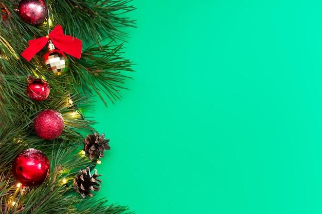 Um galho de uma árvore de natal com cones de bolas de brinquedo vermelho e dourado isolados em um fundo de cor verde