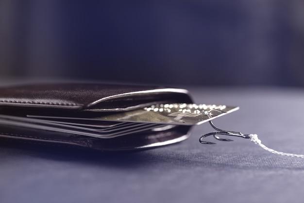 Um gancho de vara de pescar prendeu um cartão de crédito em minha carteira. roubo de dados de cartões de crédito. o hacker roubou dinheiro de um cartão de crédito.