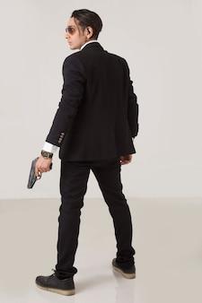 Um gangster fumando com uma arma