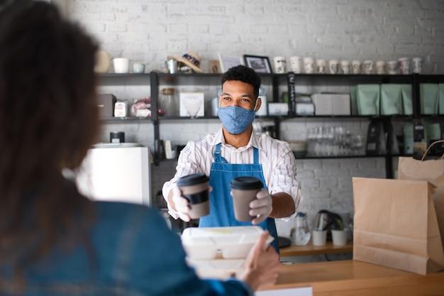 Um garçom dando comida e café embalados para levar para o cliente na cafeteria, conceito de coronavírus.