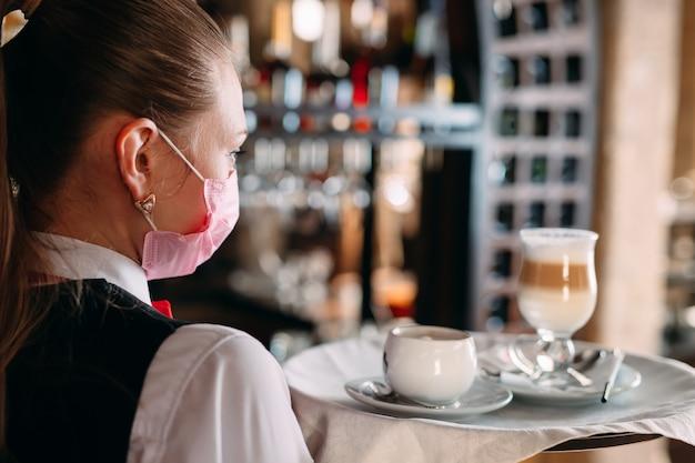 Um garçom de aparência européia em uma máscara médica serve café com leite.