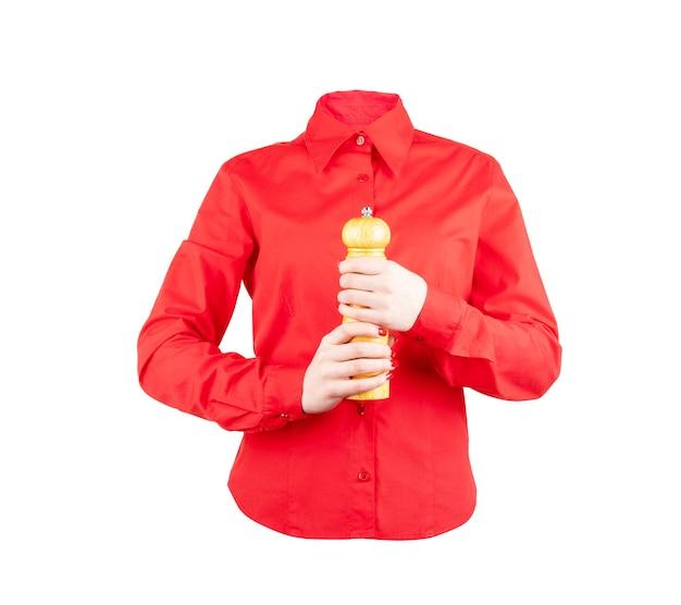 Um garçom de camisa vermelha segurando uma caixa de pimenta em um fundo branco
