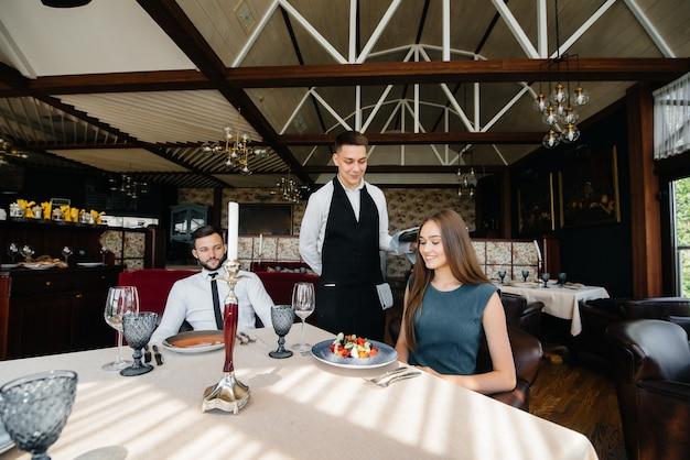 Um garçom estiloso serve um jovem casal que saiu para um encontro em um restaurante gourmet. atendimento ao cliente na área de catering.
