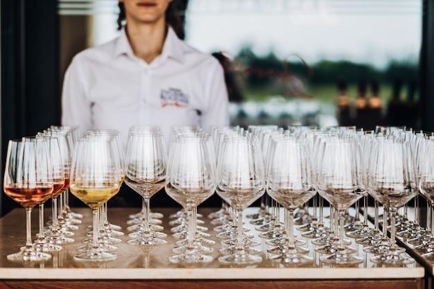 Um garçom fica atrás de muitos copos