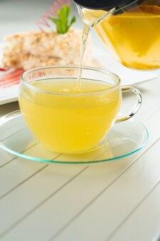 Um garçom serve chá de laranja de um bule em uma xícara transparente