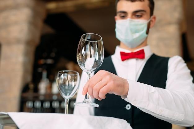 Um garçom vestindo uma máscara de proteção médica serve a mesa no restaurante