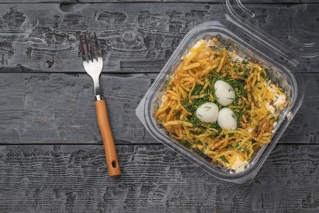 Um garfo ao lado de uma caixa de salada de plástico aberta em uma mesa de madeira