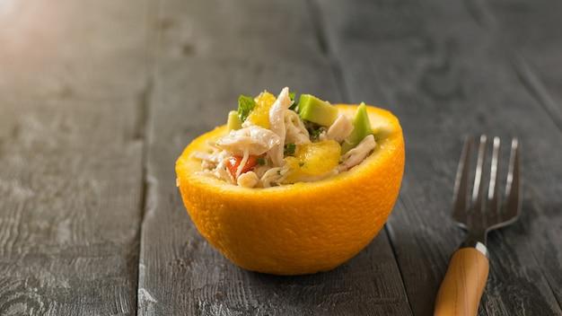Um garfo com cabo de madeira e meia laranja com salada em uma mesa de madeira