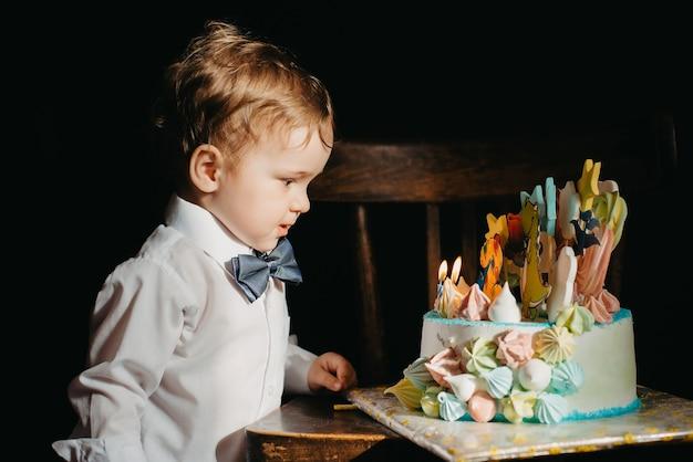 Um garotinho ao lado de um bolo de aniversário