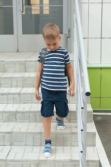 Um garotinho caminha sozinho, sai do prédio e desce a escada