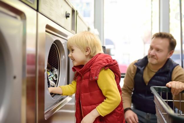 Um garotinho carrega roupas para a máquina de lavar roupa em lavandaria pública