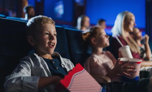 Um garotinho com a família sentado assistindo a um filme no cinema, comendo pipoca