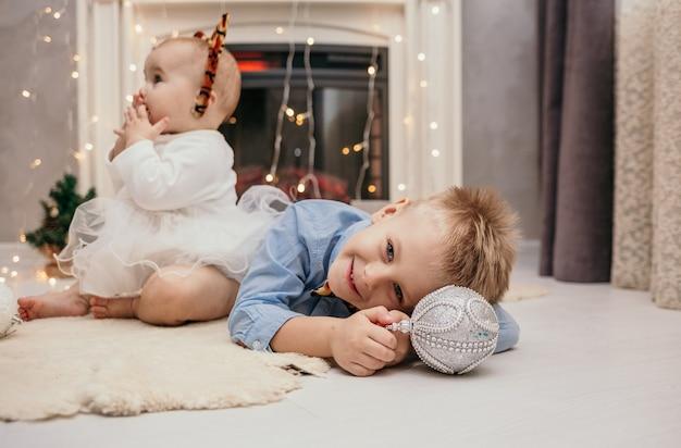 Um garotinho com uma gravata-borboleta de tigre está deitado em um tapete perto da lareira e brincando com uma árvore de natal de brinquedo