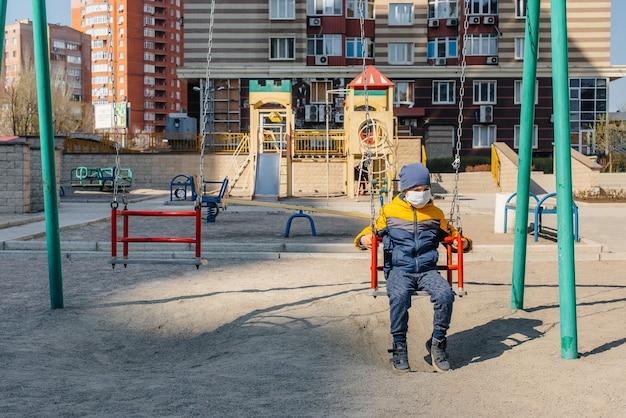 Um garotinho com uma máscara caminha no playground durante a quarentena. ficar em casa.