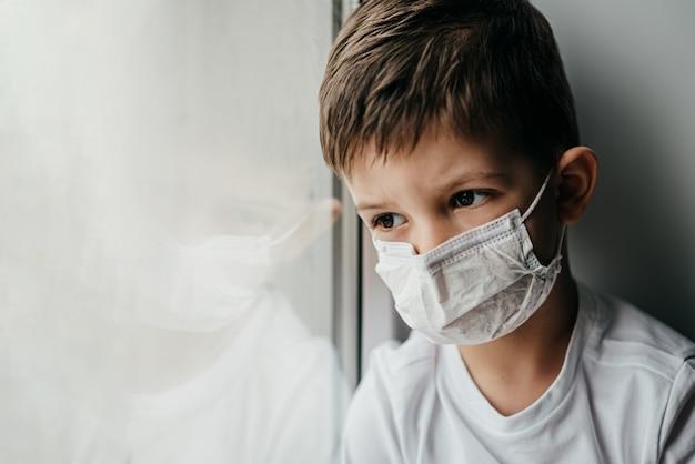 Um garotinho com uma máscara médica está sentado em casa em quarentena por causa do coronavírus e da cobertura 19 e olha pela janela.
