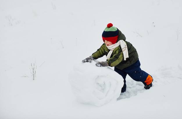 Um garotinho cria um boneco de neve