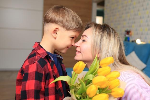 Um garotinho dá flores para sua mãe