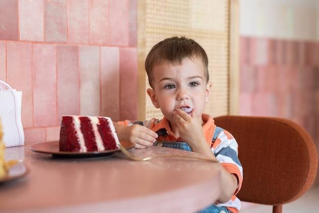 Um garotinho de 23 anos está sentado em um café e come um bolo em um pires com um grande pedaço de bolo