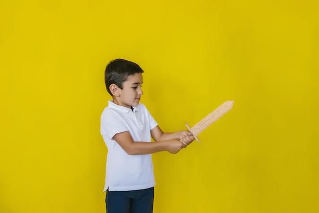 Um garotinho de camisa branca fica em pé em uma parede amarela.
