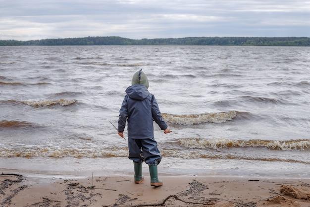 Um garotinho de casaco azul e barcos de borracha anda perto do lago