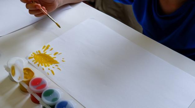 Um garotinho de óculos desenha o sol com tintas em uma folha de papel branca, sentada à mesa.