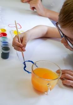 Um garotinho de óculos desenha uma nuvem com tintas em uma folha de papel branca sentada à mesa.