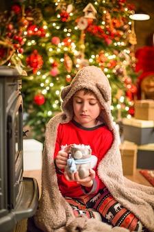 Um garotinho de pijama de natal sentado perto de uma árvore de natal