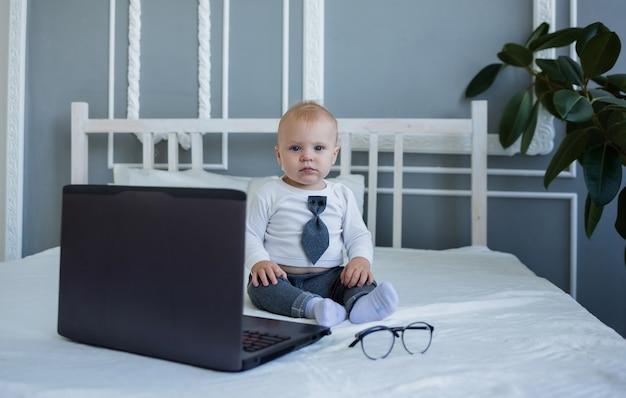 Um garotinho de terno está sentado na cama com um laptop