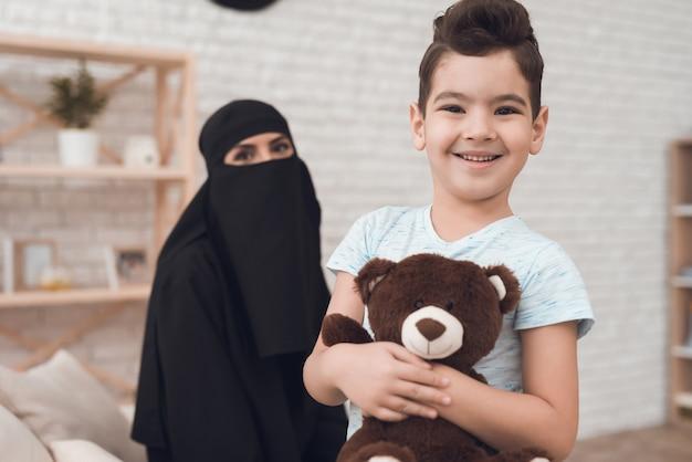 Um garotinho de uma família árabe está segurando um urso de brinquedo.