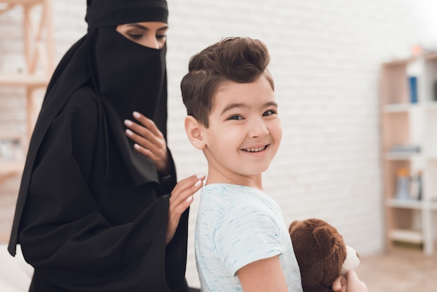 Um garotinho de uma família árabe está segurando um urso de brinquedo