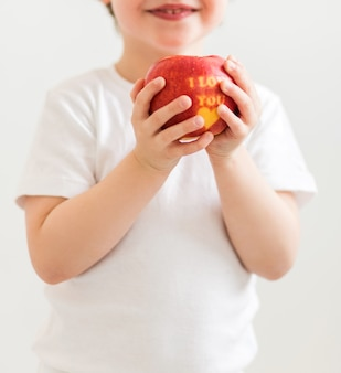 Um garotinho em uma camiseta branca tem uma maçã nas mãos com a inscrição eu te amo. foto vertical