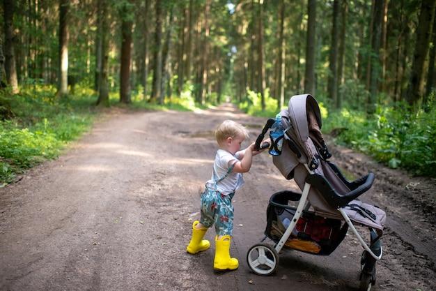 Um garotinho engraçado com botas amarelas posando com o carrinho de bebê na floresta