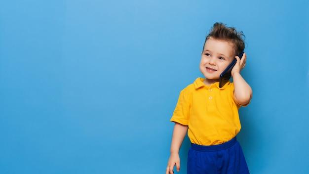 Um garotinho está falando ao celular.