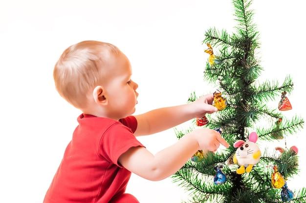 Um garotinho está procurando presentes debaixo da árvore de natal