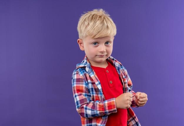 Um garotinho fofo com cabelo loiro vestindo uma camisa xadrez cerrando os punhos enquanto olha para uma parede roxa