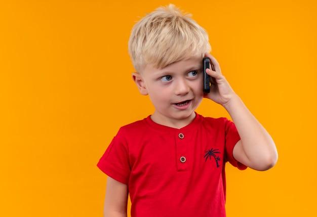 Um garotinho fofo com cabelo loiro vestindo uma camiseta vermelha falando no celular em uma parede amarela