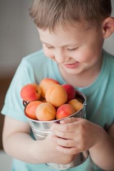 Um garotinho fofo de 4 anos comendo damascos suculentos de um balde