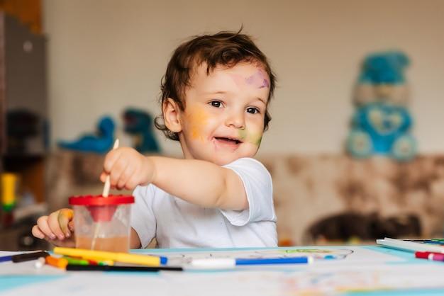Um garotinho fofo desenha com pincéis e tintas coloridas em uma folha de papel