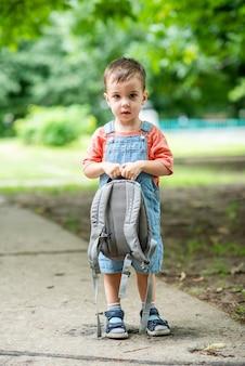 Um garotinho fofo olha para a câmera com uma bolsa nas mãos, vestindo um macacão jeans